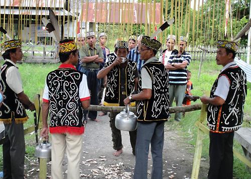 Vor dem Teilen des Balkens um ins Dayak-Taman-Langhaus zum Gawai in Melapi zu kommen muss erst einmal ein Schluck Saguer in den Rachen und auf den Boden.