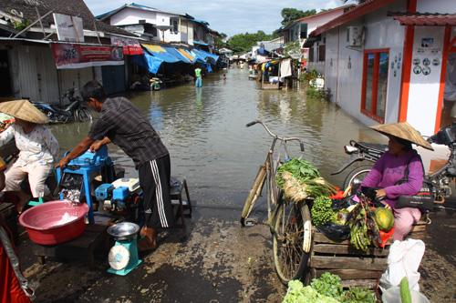 Life must go on. – Und so stehen trotz Flut einige Markttreibende an ihren Staenden.