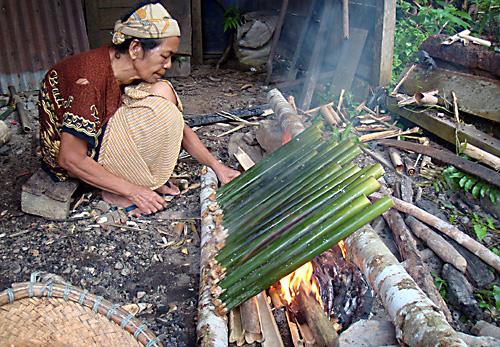 Herstellung von Pulut (Reiskuchen in Bambusstangen)