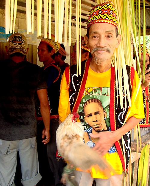 Dorfalter der die Gawai-Teilnehmer bei Eintritt ins Festhaus segnet und dabei einen Hahn vor einem im Kreis schwingt