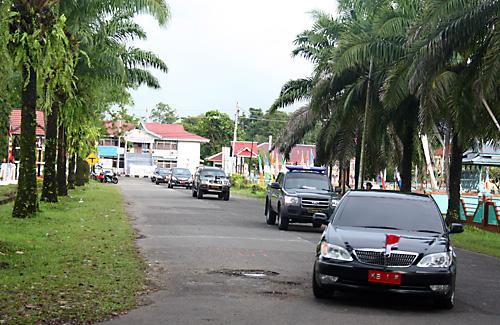 Der Bupati-Konvoi kommt durch die Oelpalmallee vorm Regierungsgebaeude vorgefahren.